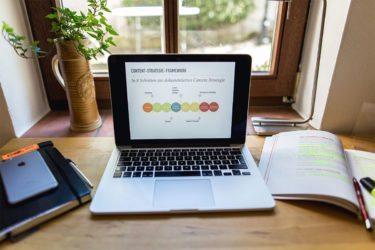Geöffneter Mac mit Content-Strategie-Framework auf Holztisch